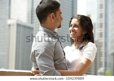 A happy Indian couple with a Chicago skyline in the background. - stock photo