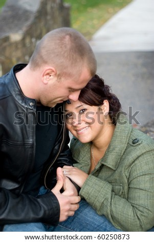 A happy interracial couple cuddling together outdoors. Shallow depth of field. - stock photo