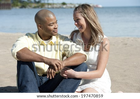 A happy interracial couple sitting at the beach on a sunny day. - stock photo