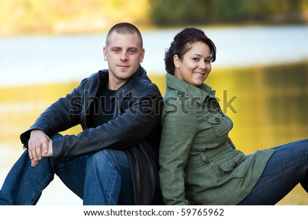 A happy interracial couple sitting outdoors by a lake or pond. - stock photo