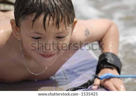 A happy kid on his body-board at the beach. - stock photo