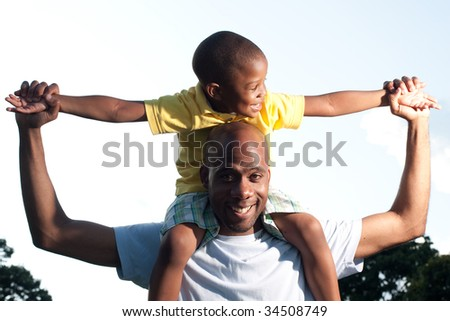 a happy kid sits on his dad's shoulders - stock photo