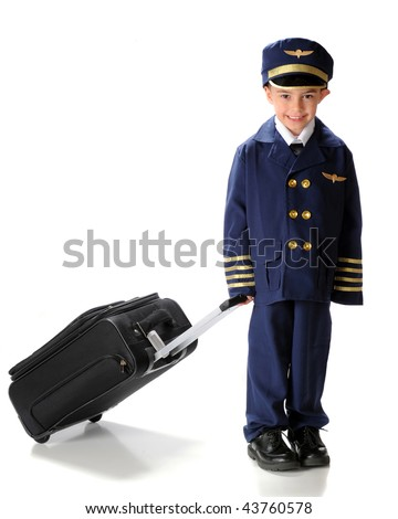 A happy, kindergarten boy toting a suitcase while dressed in an oversized airline pilot uniform.  Isolated on white. - stock photo