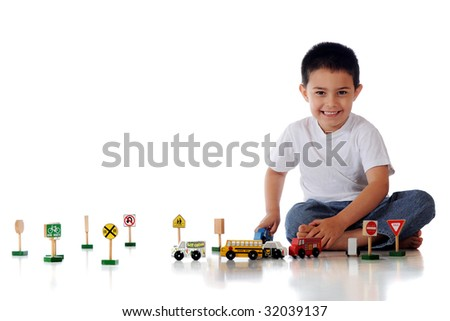 A happy kindergartner playing with an assortment of wooden cars, trucks and traffic signs.  Isolated on white. - stock photo