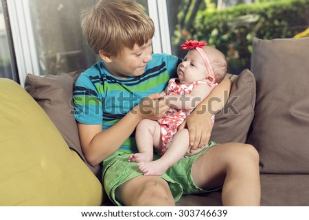 A Happy laughing boy holding his sleeping newborn baby sister - stock photo