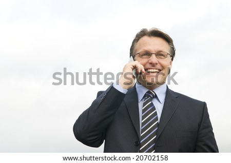 A happy laughing businessman enjoys a friendly chat on his cellphone.Space for copy. - stock photo