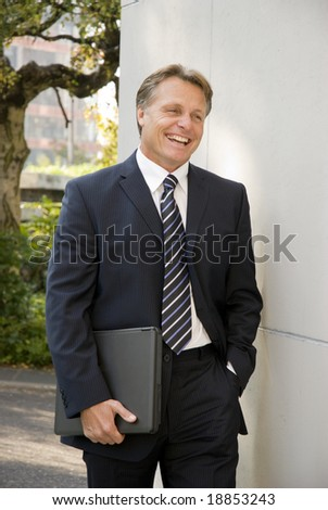A happy laughing businessman is walking along and carrying his laptop computer under his arm