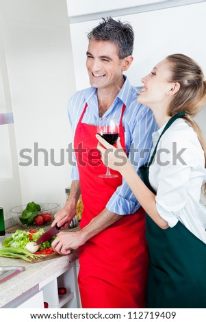 A happy laughing caucasian couple in the kitchen cooking food and drinking wine.