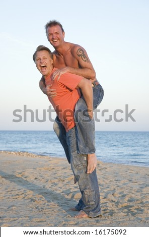 A happy laughing gay couple having fun on the beach. - stock photo