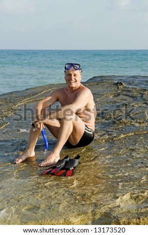 A happy laughing 44 year old man is sitting on a boulder at the beach during his vacation.