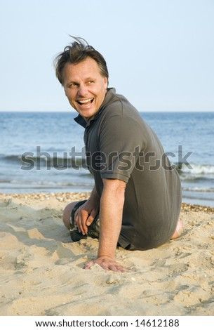 A happy laughing 44 year old man relaxing on the beach.