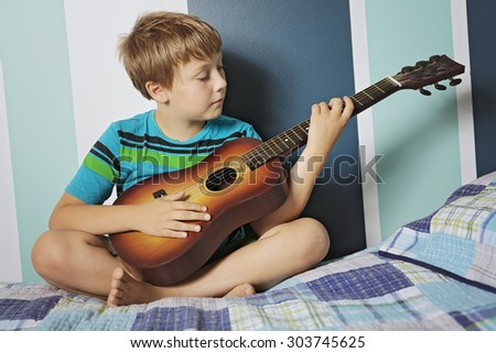 A Happy little boy playing guitar sitting in bed - stock photo