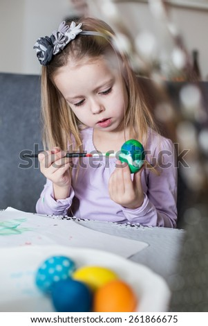 A happy little child coloring easter eggs. Cozy home atmosphere. Easter - stock photo