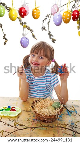 a happy little girl coloring easter eggs - stock photo