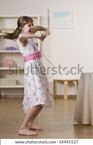 A happy little girl dancing to music.  She is listening to headphones from an Mp3 player.  Vertically framed shot. - stock photo