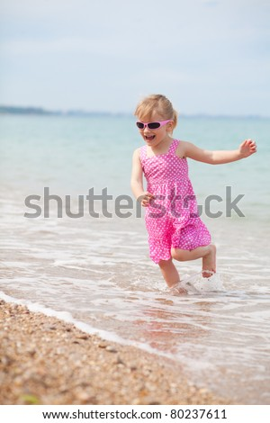 A happy little girl is running at the beach