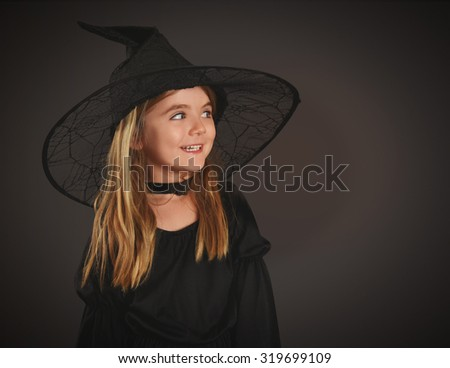 A happy little girl is wearing a witch halloween costume with a black hat isolated on a black background with copyspace fora trick or treat concept. - stock photo