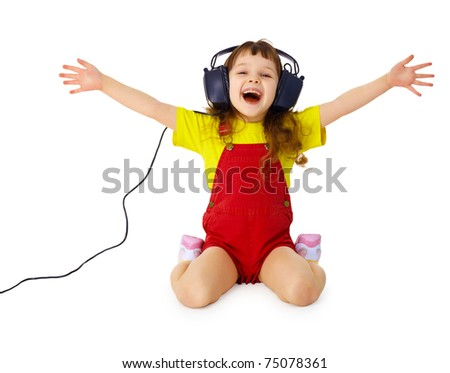 A happy little girl listens to music with headphones isolated on white background - stock photo