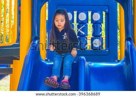 A happy little girl playing in playground at public park with greenery background - stock photo