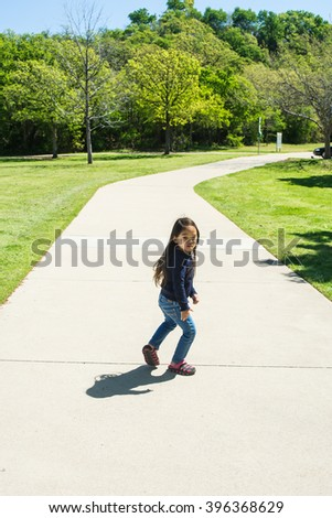 A happy little girl running at public park with greenery background - stock photo
