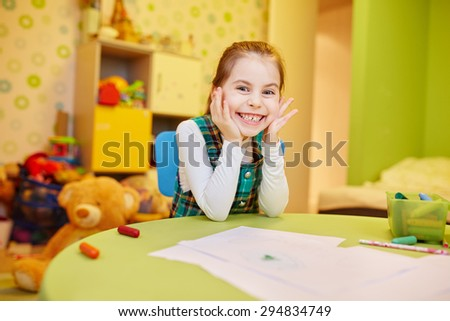 A happy little girl sitting at her table with art supplies - stock photo