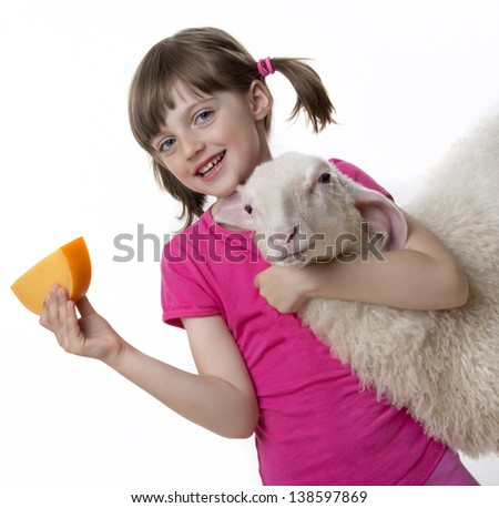 a happy little girl with a sheep and a cheese - stock photo