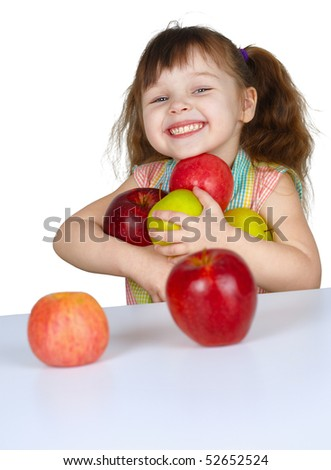 A happy little girl with apples at the table - stock photo