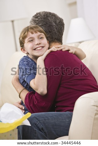 A happy-looking girl hugging her grandmother.  There is a gift bag on the coffee table.  Vertically framed shot. - stock photo