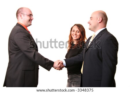 A happy looking group of three shaking hands isolated on a white background - stock photo