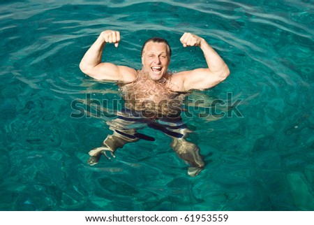 A happy lsughing forties man is striking a muscle pose while floating in the beautiful turquoise sea.