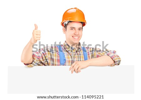 A happy male construction worker posing behind a blank panel giving thumb up - stock photo
