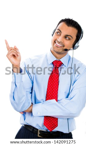 A happy male customer representative wearing phone headset is pointing at a copy space. - stock photo