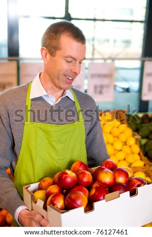 A happy male grocer with a box of ripe peaches