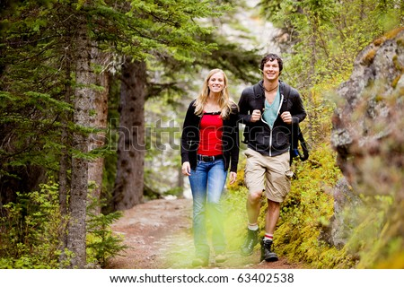 A happy man and woman hiking on a camping trip - stock photo