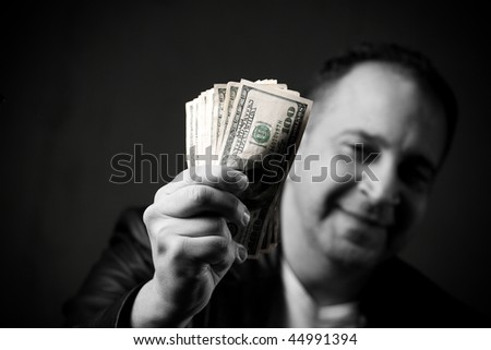 A happy man holds a handful of cash with selective color. - stock photo