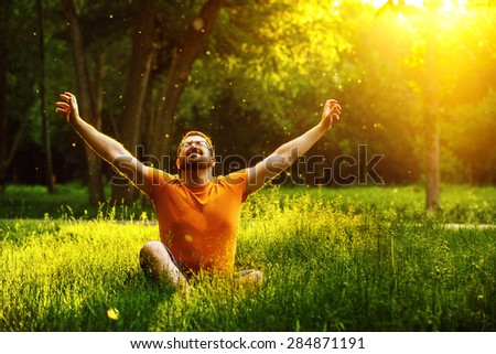 A happy man is relaxing on green grass with squint eyes and raised up to sky arms at sunny summer day at park background. Concept of wellbeing and healthy lifestyle - stock photo
