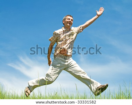 a happy man is running through the meadow