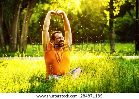 A happy man is stretching himself on green grass with squint eyes and raised up to sky arms at sunny summer day at park background. Concept of wellbeing and healthy lifestyle
