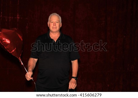 A happy man smiles while posing for his photos in a Photo Booth. Photo Booths are very popular for all parties and especially weddings. Everyone loves a good photo booth.  - stock photo