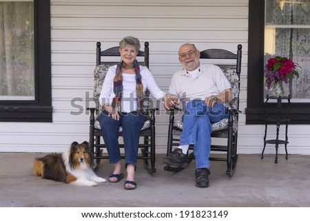 A happy married couple relax on their porch in matching rocking chairs with their Shetland sheepdog by their side. - stock photo