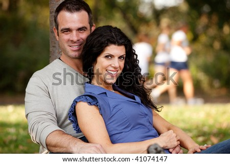 A happy married couple relaxing in the park - focus on the woman - stock photo