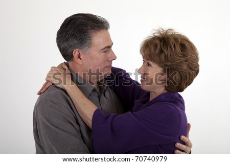 A happy mature couple smile lovingly at one another.
