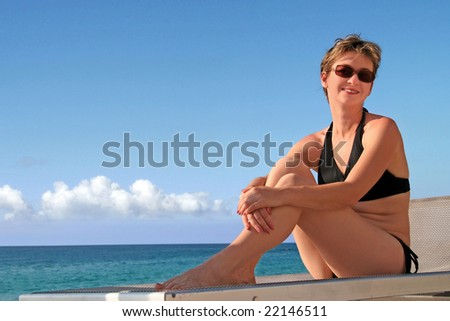 A happy mature woman relaxing on a beach by the ocean - stock photo