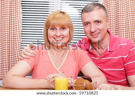 A happy middle-aged loving couple having meal in the kitchen. Focus on wife. - stock photo
