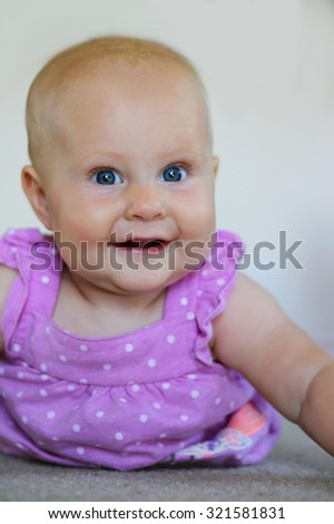 A happy 6 month old baby girl is laying on her tummy at home smiling. - stock photo