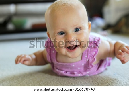 A happy 6 month old baby girl is laying on her tummy at home smiling and trying to crawl. - stock photo