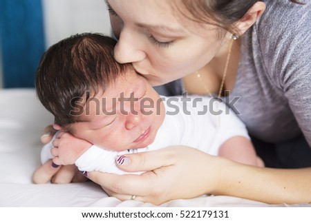 A Happy mother and baby lying on bed at home