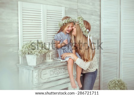 A happy mother and her young daughter are having fun. They are laughing. The girl is sitting on the fireplace.They are having floral wreathes on. The atmosphere of happiness is all around them. - stock photo