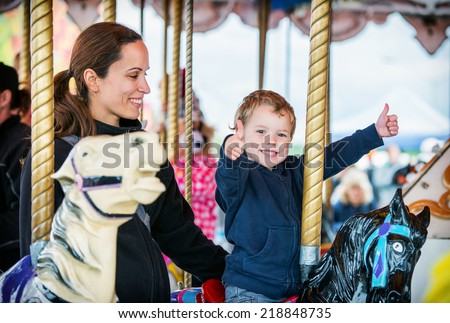 A happy mother and son are riding on a merry-go-round carousel together, smiling and having fun at a fair or amusement park.  The boy holds two thumbs up.  - stock photo