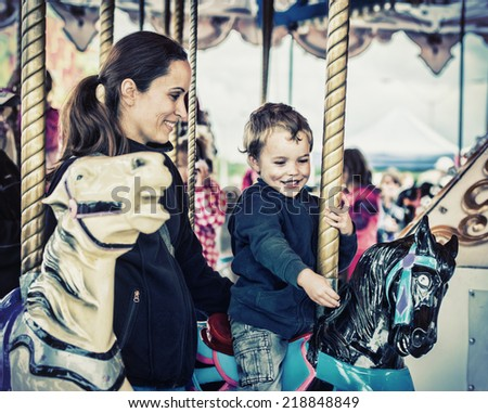 A happy mother and son are riding on a merry-go-round carousel together, smiling and having fun at a fair or amusement park.  Filtered for a retro, vintage look.  - stock photo